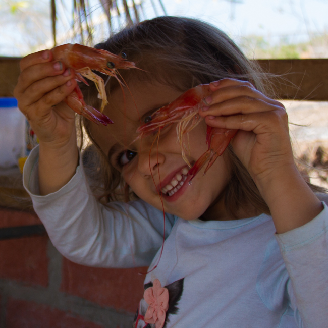 Eva helping to pick shrimp for dinner at the market