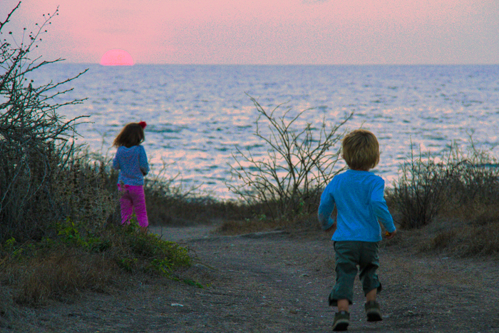 Eva and Coco run to catch the last glimpse of the setting sun
